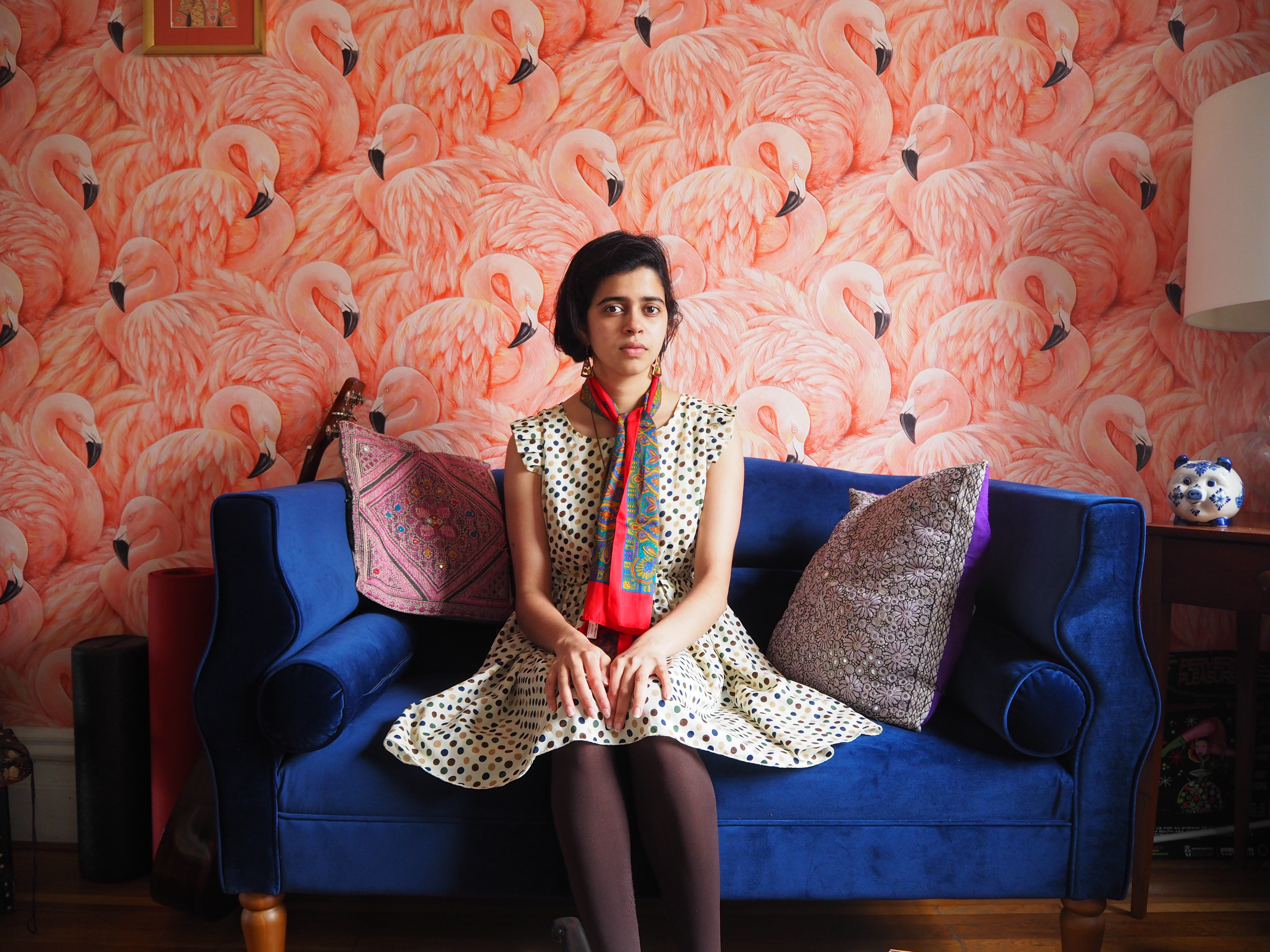 Photo of Aditi sitting on a velvet blue couch in a polka dot dress, with a flamingo wallpaper backdrop.
